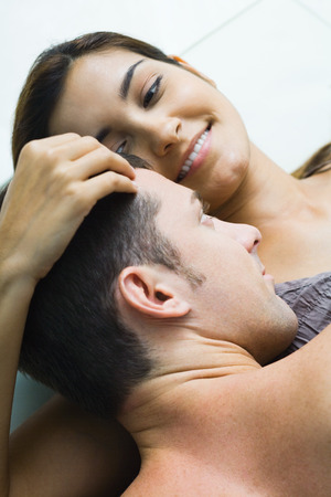 Man lying on top of woman, woman holding his head, smiling, high angle view LANG_EVOIMAGES