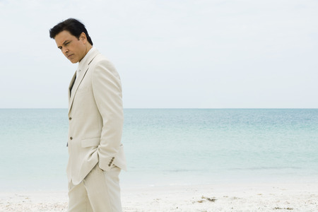 Businessman standing on beach with hands in pockets, looking down