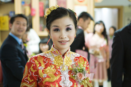 Bride dressed in traditional Chinese clothing, smiling at camera, portrait