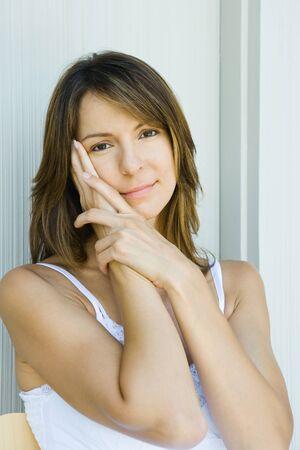 Woman holding face, smiling at camera