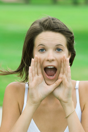 Teenage girl shouting, hands raised to mouth, looking at camera
