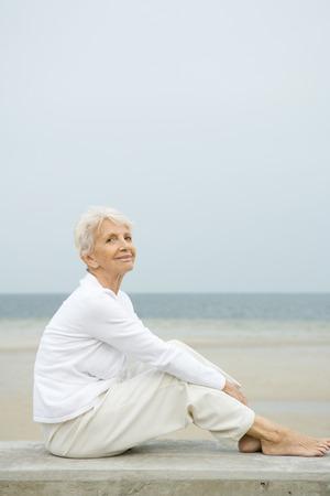 Descalza, mujer mayor, sentado, en, pared baja, sonriente, playa, en, fondo, longitud completa LANG_EVOIMAGES