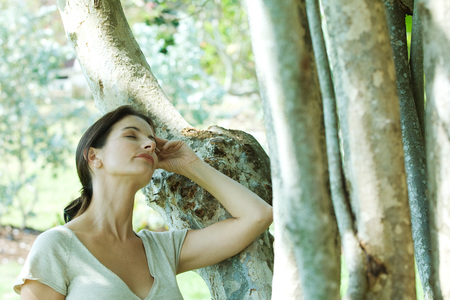 leaning against: Woman leaning against tree trunk, head back, eyes closed LANG_EVOIMAGES