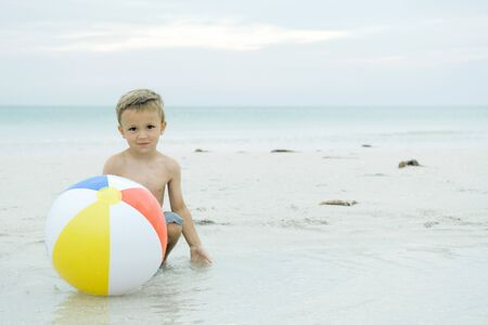 Little boy crouching behind ball at the beach, smiling at camera