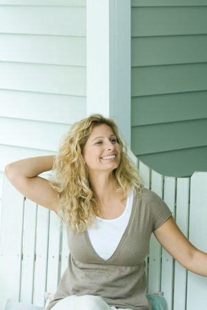 Woman sitting on bench with hand behind head, smiling, looking away