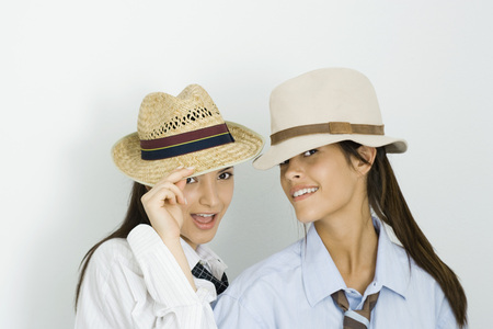 Two young female friends wearing hats and ties, both smiling at camera