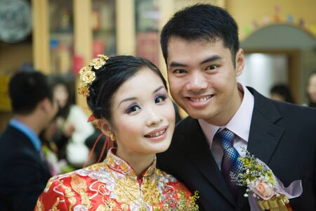 Newlyweds smiling at camera, bride dressed in traditional Chinese clothing