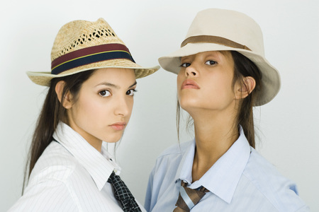 accusations: Two young female friends wearing hats and ties, both looking at camera