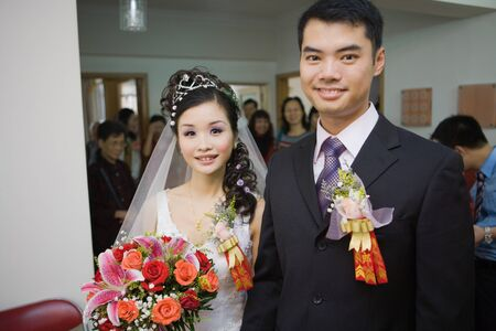Bride and groom wearing corsages, smiling at camera, friends and family in background
