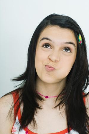 Teenage girl looking up with puffed cheeks, portrait