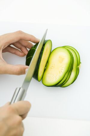 personal perspective: Hands cutting summer squash (zapallito redondo), with knife, cropped view