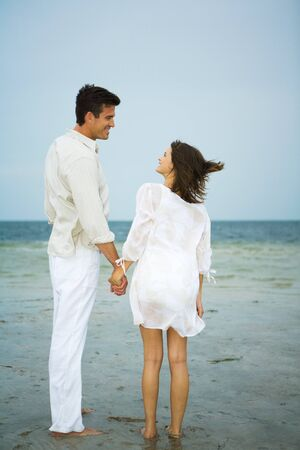 Man and young female companion on beach, holding hands, looking at each other, full length