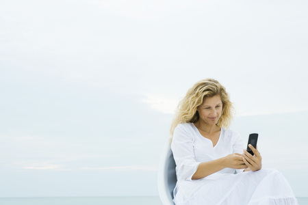 Woman sitting in chair outdoors, looking at cell phone