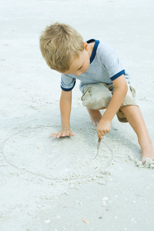 Little boy crouching at the beach, drawing in sand with stick