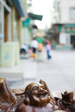 Laughing Buddha statue, street in background LANG_EVOIMAGES