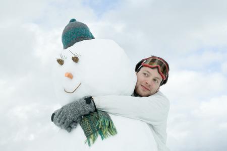 Hombre joven, abrazar, muñeco de nieve