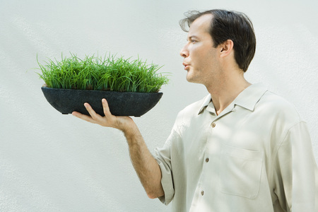 holistic view: Man blowing on potted wheat grass, profile
