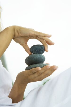 Person stacking pebbles in hand, cropped view LANG_EVOIMAGES