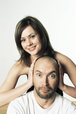 Woman covering mans ears with her hands, smiling, both looking at camera