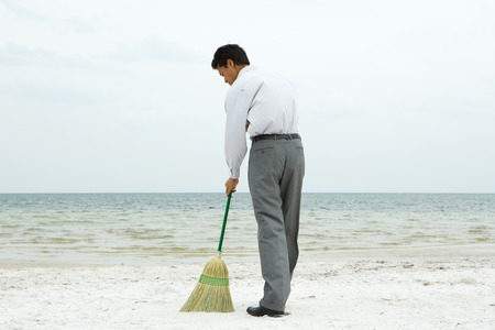 Man standing on beach sweeping with broom, rear view