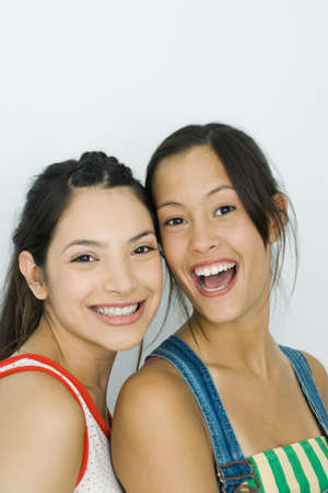 Two young friends smiling at camera, portrait