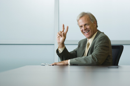 leaning against: Businessman making peace sign, smiling at camera