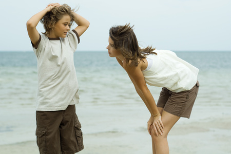 Brother and sister standing face to face at the beach, boy with hands behind head