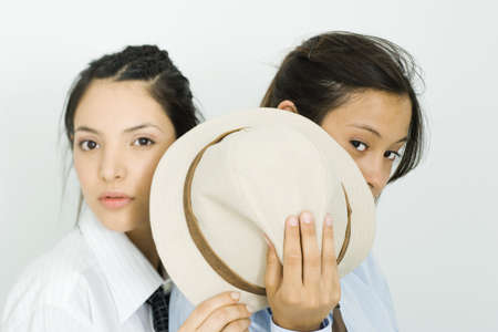 Two young female friends hiding behind hat, looking at camera