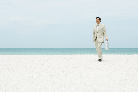 Businessman walking across beach, carrying briefcase