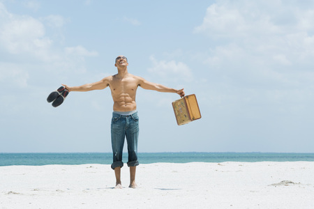 edge: Man standing at the beach, holding up shoes and suitcase, head back