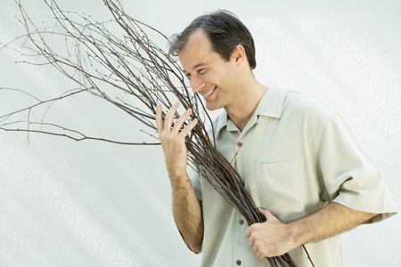 Man holding armful of twigs, smiling, looking away