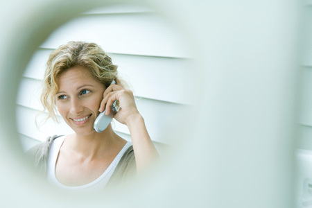 Woman using cell phone, smiling, viewed through hole