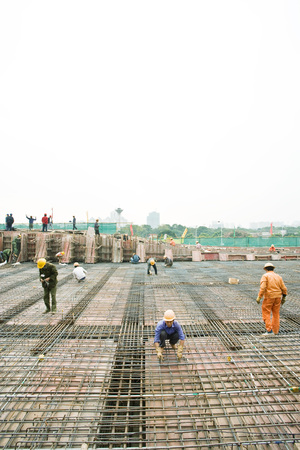 Workers building steel framework at construction site