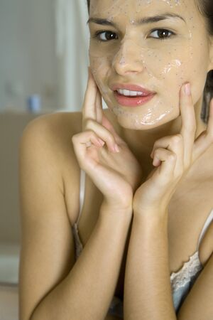 Young woman applying facial mask, looking at camera, cropped view LANG_EVOIMAGES