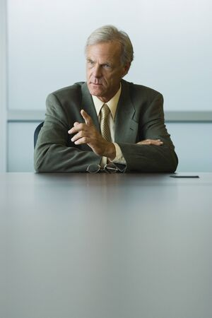 Businessman seated, furrowing brow and pointing finger