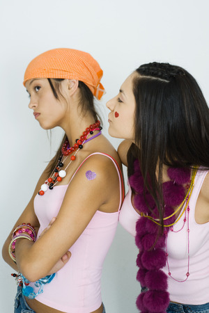 Teenage girl standing with arms folded, friend standing behind and looking over her shoulder