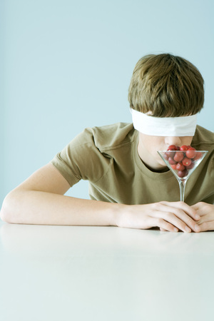 Young male wearing blindfold, smelling glass full of cherry tomatoes