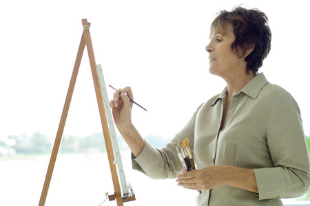 deftness: Woman painting on canvas, side view, close-up