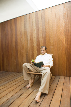 Man sitting in lounge chair reading book, apple in hand LANG_EVOIMAGES