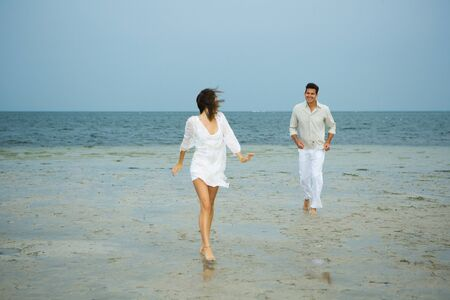 Man and young female companion on beach, walking toward camera, man in background, full length