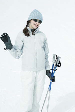 skiers: Teenage girl with ski gear, waving at camera, portrait LANG_EVOIMAGES