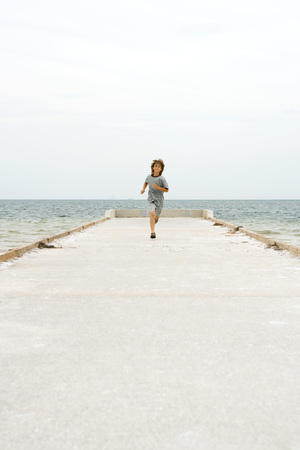 Boy running on pier, towards camera, ocean in background LANG_EVOIMAGES