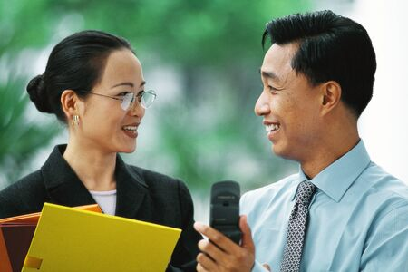 Businessman showing cell phone to female colleague, both smiling at each other