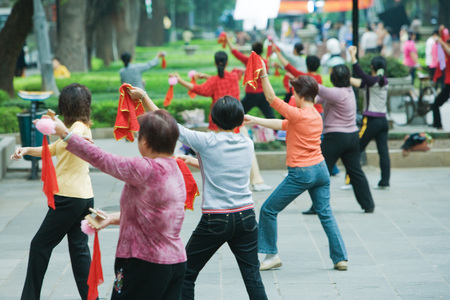 China, Guangzhou, group of woman practicing tai chi chuan outdoors, rear view