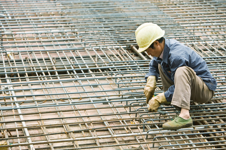 connecting rod: Man crouching at construction site, building steel framework