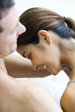 Couple laughing together, womans head lowered, cropped view