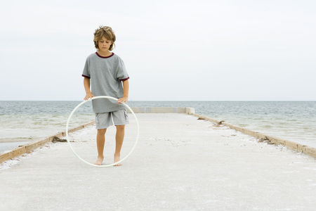 Boy standing on pier playing with plastic hoop, full length