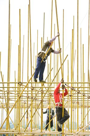 connecting rod: Workers assembling metal scaffolding at construction site