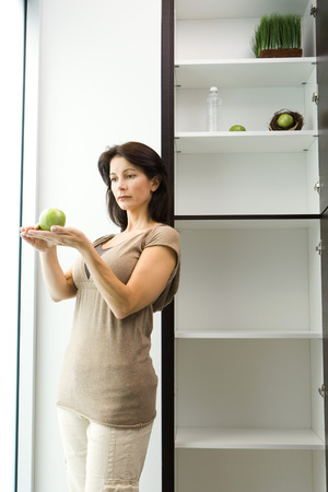 Woman standing by open pantry, apple on palms of hands