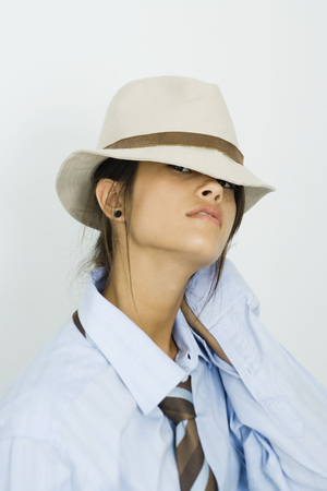 Teenage girl wearing tie, looking out from under hat at camera